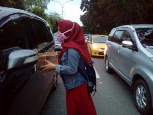 Aktivis PMII Kota Pontianak tengah mengangsurkan kotak sumbangan ke pengemudi mobil, Rabu (21/12/2016).