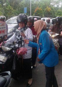 Aktivis Korps PMII Putri sedang memberikan sekuntum bunga kepada pengendara sepeda motor di Jalan Ayani, Kamis (22/12/2016).